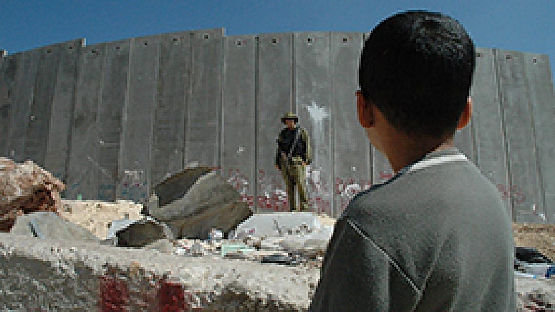 ילד פלסטיני וחייל ישראלי ליד גדר ההפרדה. צילום: אימג'בנק/ Getty Images