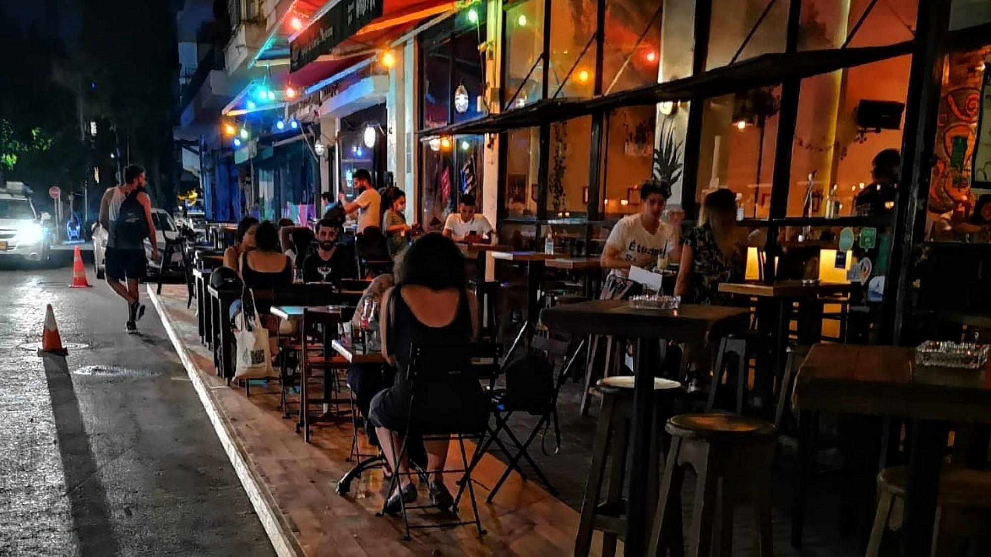 רמפות עץ מפרידות את המסעדה מהכביש. הפיילוט של העירייה ברחוב ויטל (צילום: יונתן בנדיגר)