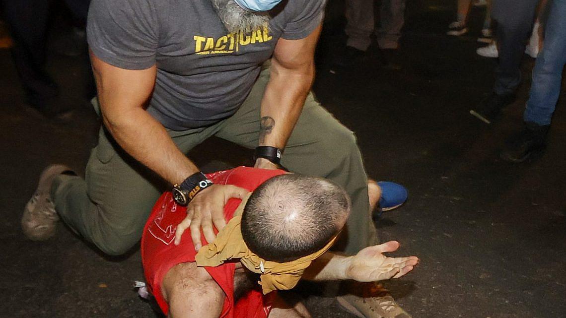 """שוטר סמוי מתנפל על מפגין. צעדת המחאה במוצ""""ש (צילום: ג'ק גואז\גטי אימג'ס)"""