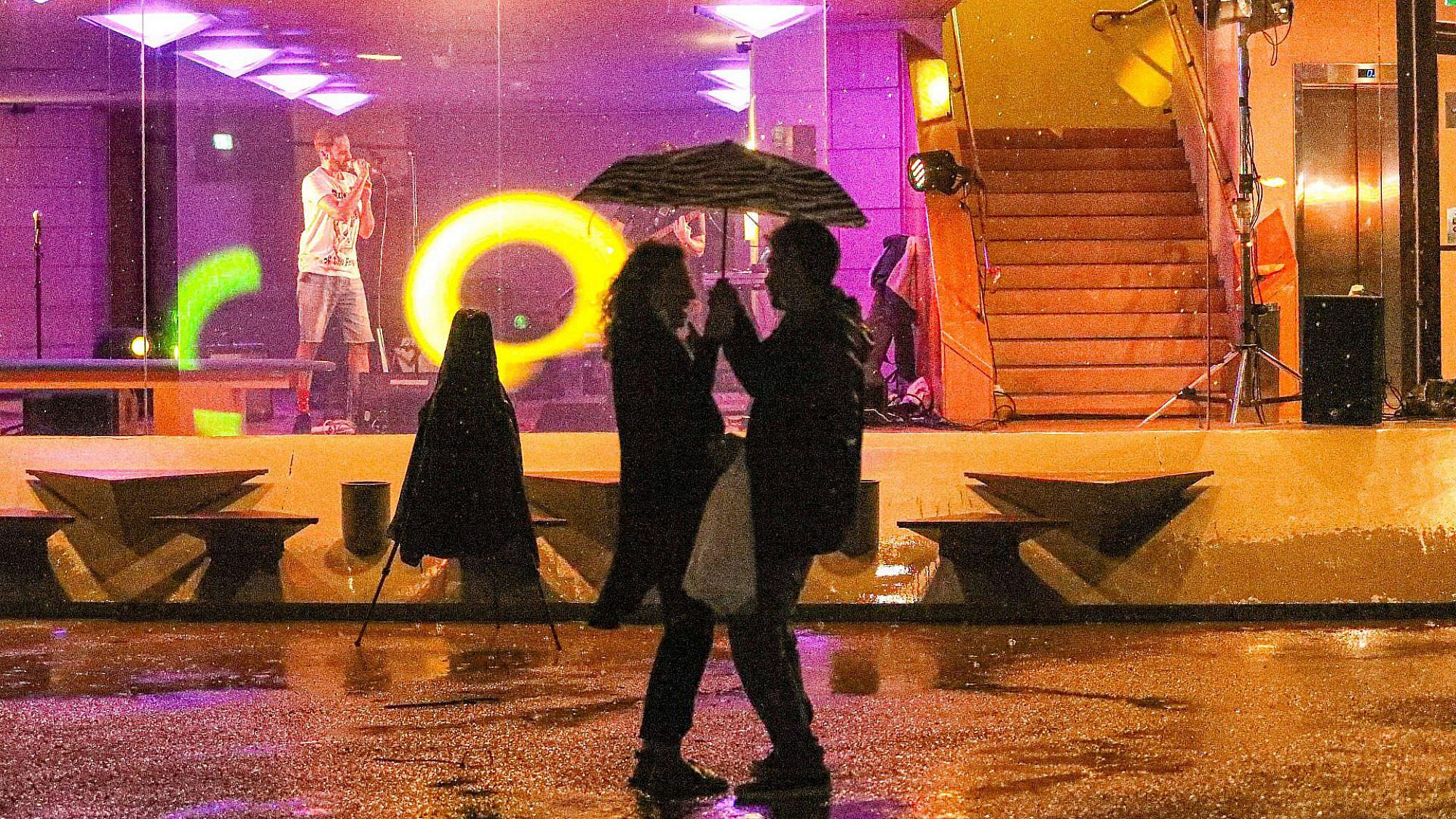 זוג מתחת למטריה בהופעה במרכז ענב. צילום: שלומי יוסף