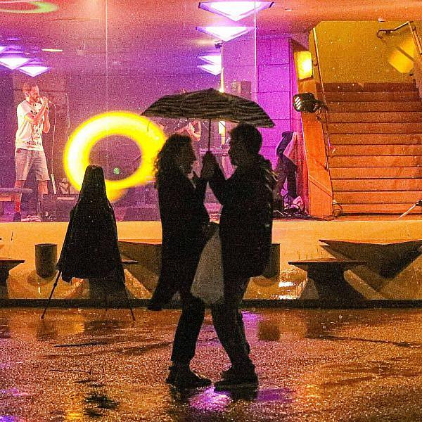 זוג מתחת למטריה במרכז ענב, אמש. צילום: שלומי יוסף