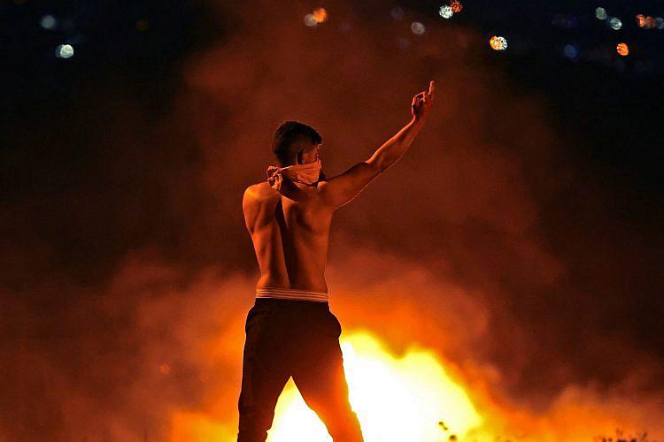 את רואה שרה, אפשר לשרוף את המדינה גם בלי לרדת מהארץ. נער פלסטיני בהתנגשויות במחסום חווארה (צילום: ג'עפר אישטייה\AFP\גטי אימג'ס)