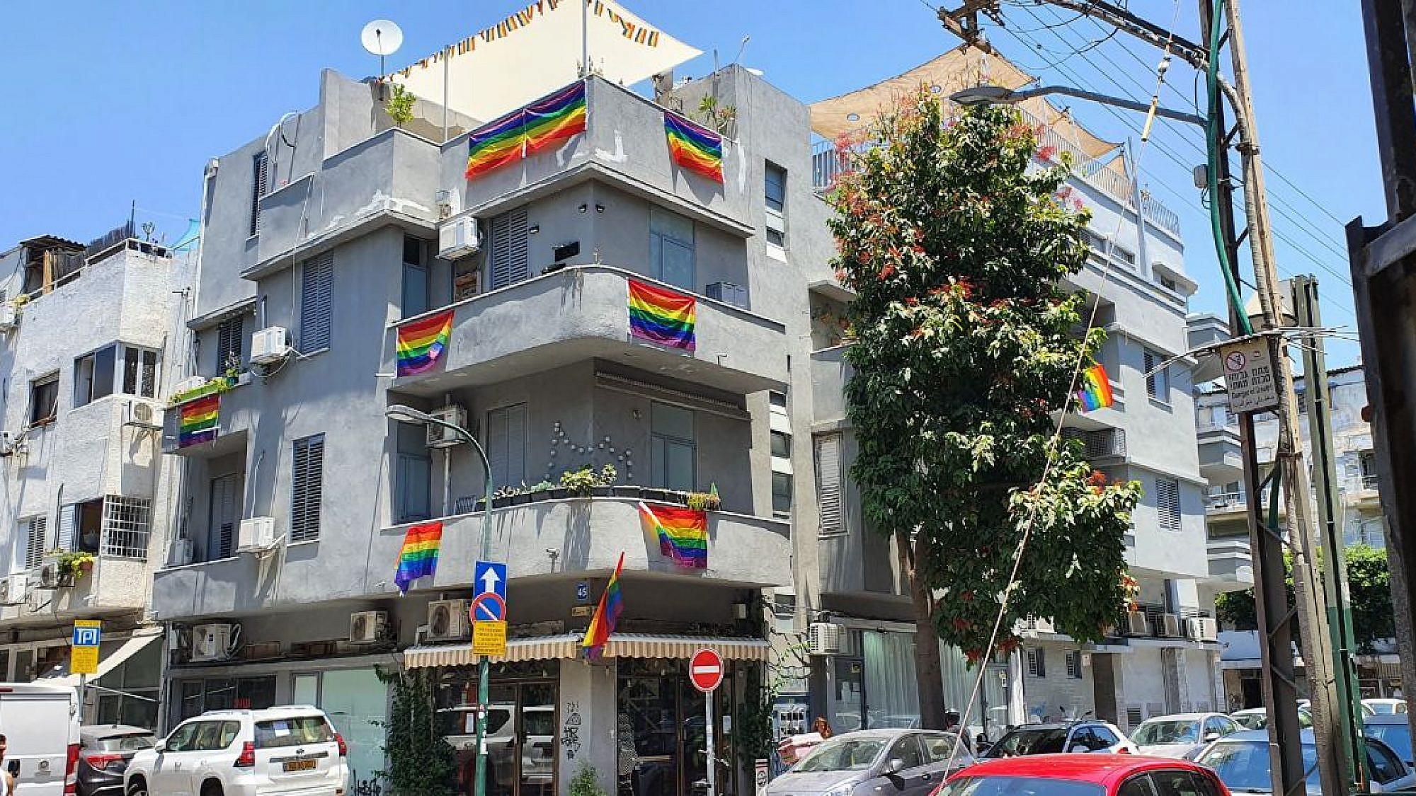 עשרה דגלי גאווה, ועוד אחד מאחורי העץ. שכונת פלורנטין בדרום תל-אביב, יוני 2021 (צילום: אורי וולטמן)